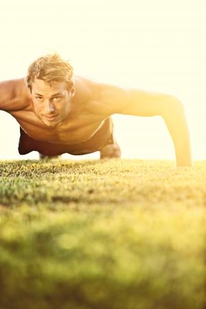 hombre deportista: Pectorales deporte de fitness hombre haciendo flexiones. Atleta masculino ejercicio empuje hacia arriba fuera de la luz del sol soleado. Coloque Modelo masculino descamisado en crossfit ejercicio al aire libre. Concepto de estilo de vida saludable.