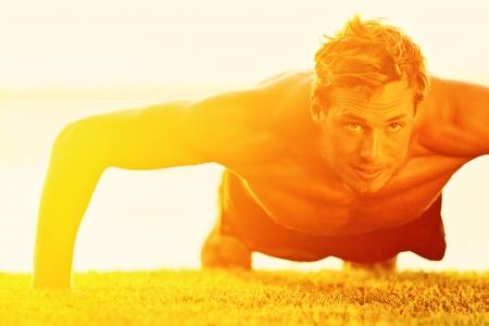 スポーツ フィットネス男腕立て伏せ。オスの運動選手のプッシュを行使日当たりの良い日差しで外に。Crossfit 運動屋外で上半身裸の男性フィットネ