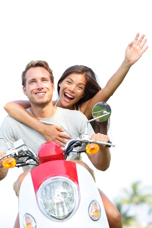 scooters: Young couple on scooter in love and happy together. Joyful mixed race couple having fun together outside driving motorcycle scooter. Interracial couple, Asian woman, Caucasian man. Stock Photo