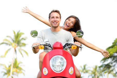 Happy free freedom couple driving scooter excited on summer holidays vacation. Young multiethnic couple in love, Asian woman, Caucasian man photo