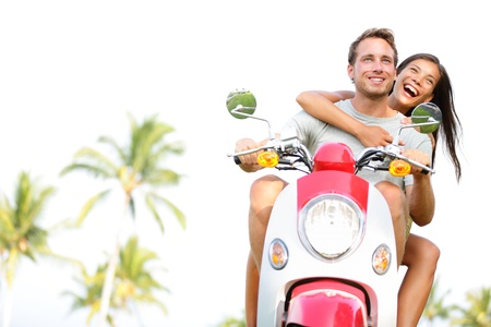 Free young couple on scooter happy on summer vacation holidays. Multiethnic cheerful couple having fun driving scooter together outdoors. Lifestyle image with Caucasian man, Asian woman.