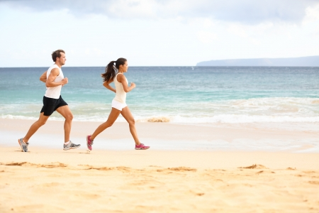 Running people - woman and man athlete runners jogging in sand on beach. Fit young fitness couple exercising healthy lifestyle outdoors. Male athlete and female fitness model training together. Stock Photo - 20560059