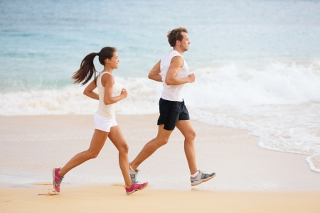 sporty: People running - runner couple on beach run jogging outdoors. Fit man athlete and woman fitness runners working out together running on beautiful beach. Multi-ethnic couple.
