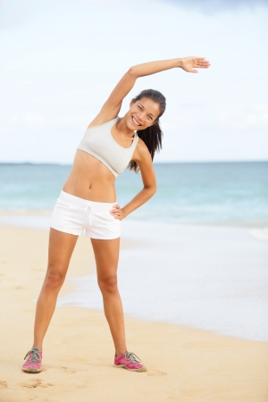Fitness woman exercising training on beach stretching during exercise. Beautiful woman living healthy lifestyle working out outside. Happy smiling fit multiracial Asian Caucasian sport model. Stock Photo - 20560055