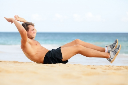 situp: Fitness man doing crunches sit-ups on beach exercise outside. Fit male athlete exercising sit ups training on beautiful beach. Handsome sport model in cross training workout outdoors.