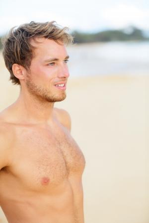 hombre sin camisa: Playa Hombre mirando al mar disfruta de la visión de pie sin camisa y guapo. El ajuste del modelo masculino de la aptitud en la playa hermosa.