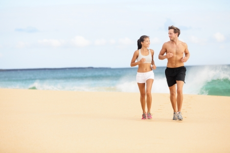 Running people. Runners couple on beach run jogging training. Fit man athlete and woman fitness runner working out together running and talking having fun on beautiful beach. Multiracial couple. Stock Photo