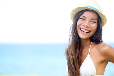 Woman - happy joyful beach summer girl portrait. Laughing lovely smiling multiracial young female model looking excited at camera wearing hipster hat by the ocean sea on sunny summer day by the water. Stock Photo - 20560056