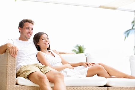 outdoor living: Couple relaxing together in sofa. Romantic young happy multi-ethnic couple lying at home in sofa resting having fun together maybe watching tv. Asian woman, Caucasian man.