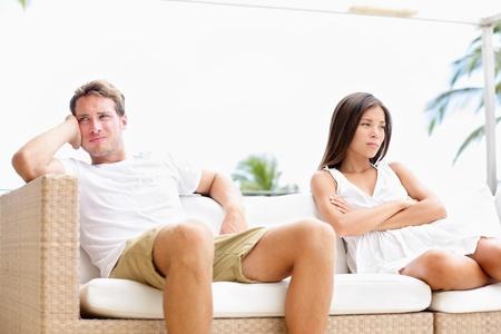 angry couple: Pares infelices molesto con problemas maritales enojados y loca que tiene conflicto tras argumento. Pareja joven multirracial, mujer asi�tica, hombre blanco cauc�sico.
