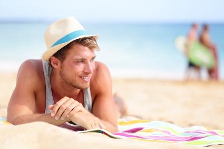 uomo felice: L'uomo sulla spiaggia situata nella sabbia alla ricerca di lato sorridente felice di indossare pantaloni a vita bassa cappello di estate. Giovane modello maschio godendo le vacanze estive viaggi in riva all'oceano.