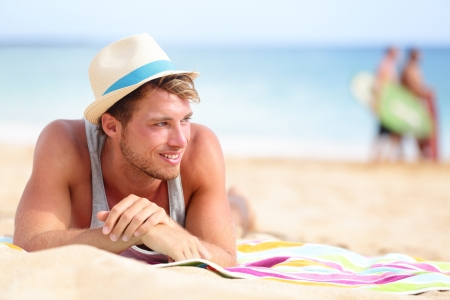 Man on beach lying in sand looking to side smiling happy wearing hipster summer hat. Young male model enjoying summer travel holiday by the ocean. Stock Photo