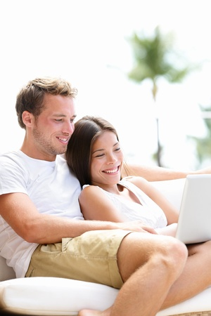 Couple relaxing together in sofa with laptop pc computer having fun. Romantic young happy multiracial couple lying at home in sofa resting having fun together maybe watching movie. Man and woman. photo