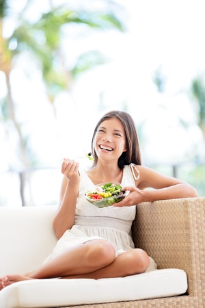 Healthy lifestyle woman eating salad smiling happy outdoors on beautiful day. Young female eating healthy food outside in summer dress laughing and relaxing in sofa. Pretty multiracial model. photo