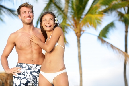 Romantic couple on happy beach travel standing smiling in swimwear. Beautiful young multi-ethnic couple, Asian woman and Caucasian man having fun together on summer holidays vacation travel.