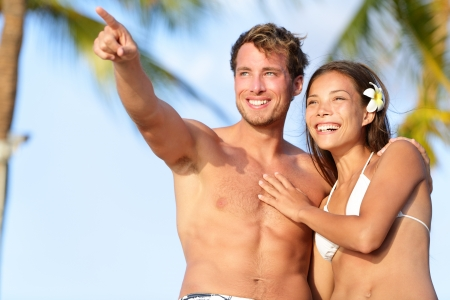 Couple on beach happy in swimwear, man pointing showing and looking at view. Beautiful young multi-ethnic couple, Asian woman and Caucasian man having fun together on summer holidays vacation travel. photo