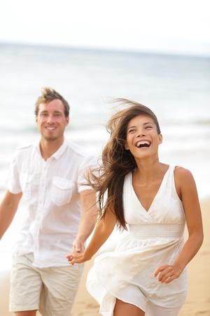 erwachsene: Beach fun - Paar lachend und zusammen laufen im Sommer urlaub Urlaub auf der schönen goldenen Strand. Joyful aufgeregt multiethnischen Paar, asiatische Frau und Mann kaukasischen.
