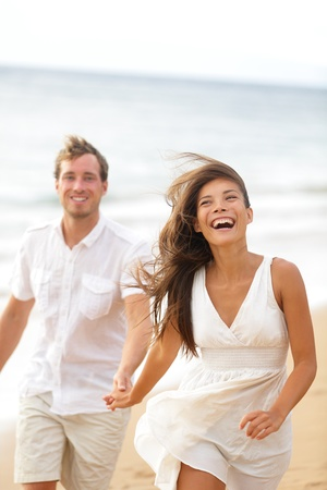 Beach fun - couple laughing and running together during summer travel vacation holiday on beautiful golden beach. Joyful excited multi-ethnic couple, Asian woman and Caucasian man.