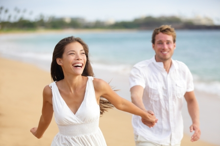 Beach couple running having fun laughing together during summer travel vacation holiday on beautiful golden beach. Joyful excited multi-ethnic couple, Asian woman and Caucasian man. photo