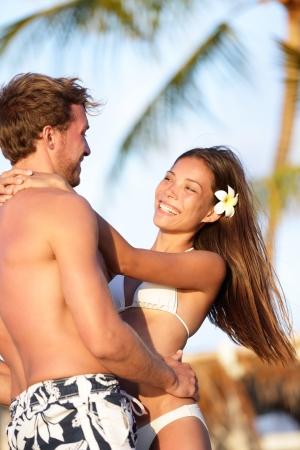 ビーチのカップルで繋いで笑みを浮かべて、お互いの周り幸せなハワイの熱帯のビーチで休暇の夏の楽しみを持って大好きです。美しい若い混血カ