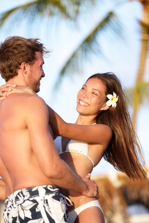 interracial relationships: Beach couple in love having vacation summer fun holding hands around each other smiling happy on tropical beach on Hawaii. Beautiful young multiracial couple, Asian woman, Caucasian man. Stock Photo