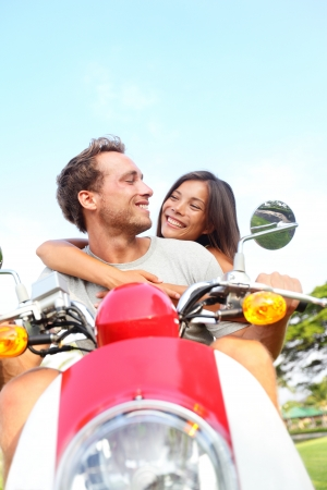 Young couple driving scooter in love. Joyful mixed race couple having fun together outside driving motorcycle scooter. Free happy interracial couple on vacation. Asian woman, Caucasian man. photo