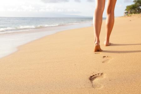 해변 여행-모래에 발자국을 떠나는 모래 해변에 산책하는 여자. 여성 피트와 Kaanapali 해변, 마우이, 하와이, 미국에 황금빛 모래의 근접 촬영 세부 사항. 스톡 콘텐츠