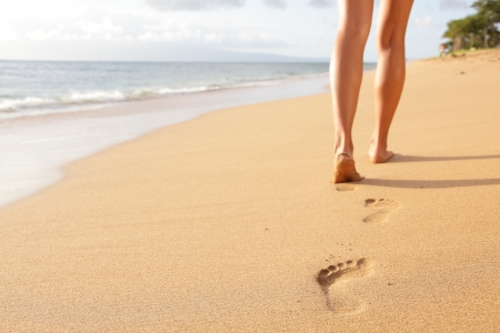 huellas de pies: Viajes Playa - la mujer caminando en la playa de arena dejando huellas en la arena. Detalle del primer de pies femeninos y arena dorada en la playa de Kaanapali, Maui, Hawai, EE.UU..