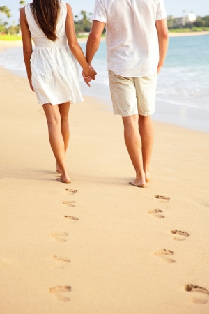 Couple holding hands walking romantic on beach on vacation travel holidays leaving footprints in the sand. Closeup of feet and golden sand for copy space. Young couple wearing white shorts. photo