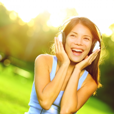 sing: Woman listening to music in headphones in park in beautiful sunlight on sunny day. Happy joyful asian woman singing outside.
