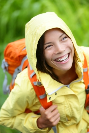 woman hiking: Happy hiker woman hiking in rain with backpack smiling candid and real. Fresh girl trekking in autumn forest. Beautiful smile on mixed race Asian Caucasian female model.
