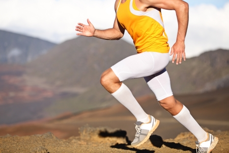 athletic body: Running sport fitness man. Closeup of strong legs and shoes in action. Male athlete fitness runner sprinting fast outside in compression sports clothing, socks and tights shorts. Trail running concept