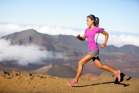 Female running athlete. Woman trail runner sprinting for success goals and healthy lifestyle in amazing nature landscape. Cross country run with fit female fitness model running at fast speed. Stock Photo