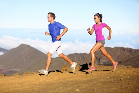 run woman: Running sport - Runners couple in trail run outside in amazing nature. Fit young sports multiracial fitness couple training cross country running together. Asian woman, Caucasian man in full body. Stock Photo