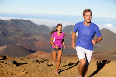 Running sport - trail runners in cross country run. Man and woman couple athletes training in amazing nature landscape. Fit male fitness model and female athlete working out facing challenges. photo