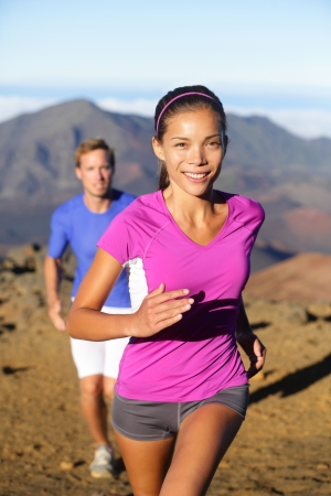 Trail running woman runner. Healthy lifestyle concept with runners couple trail running outside in beautiful landscape. Happy smiling female sports fitness runner and man in background, Stock Photo - 20617409