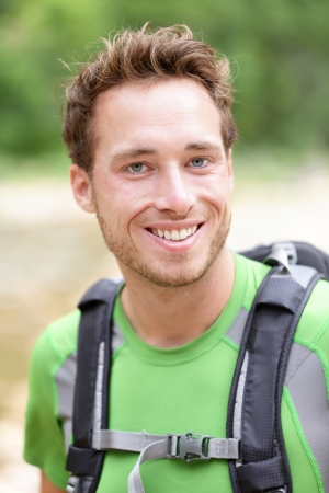 Hiker man portrait of outdoors hiking sporty guy smiling happy at camera wearing backpack outdoors during hike in forest nature. Caucasian male model outside. photo