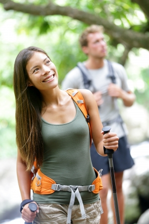 Couple hiking in forest during travel. Happy woman hiker looking at beautiful nature landscape while trekking traveling in Iao Valley State Park, Maui, Hawaii, USA. Multiracial couple, Asian woman. photo