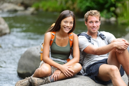 People hiking - resting hikers portrait at river. Portrait of woman and man hiker looking at camera smiling happy after a hike in Iao Valley State Park, Maui, Hawaii, USA. Interracial couple dating. photo