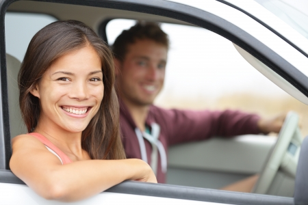 man driving: Cars - couple driving in new car smiling happy looking at camera. Young people on road trip drive in car. Beautiful interracial couple in their twenties, Asian woman, Caucasian man.