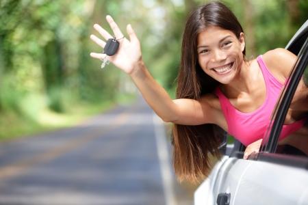 Auto - eine Frau, neue Autoschlüssel glücklich lächelnde road trip nach dem Aufstehen Führerschein. Schöne junge Fahrschüler kommen aus dem Fenster hält Autoschlüssel aufgeregt.