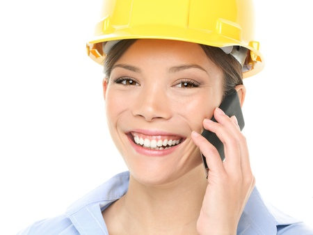 Engineer or architect Portrait of beautiful young woman wearing hardhat using mobile phone isolated over white background photo