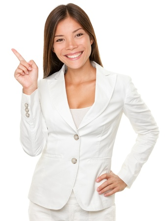 sideways: Portrait of happy young businesswoman with hand on hip pointing sideways over white background Stock Photo