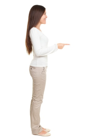 Full length side view of young woman pointing at copyspace isolated over white background Imagens