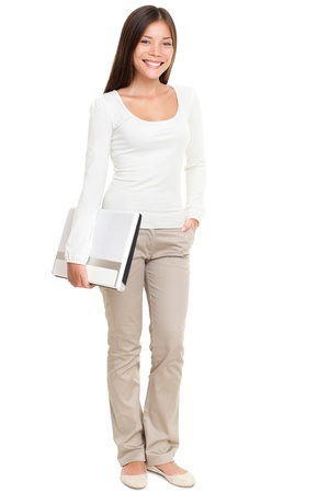 Full length portrait of beautiful young woman holding laptop isolated over white background photo