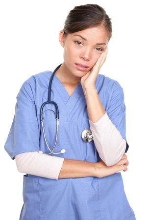 Ongelukkig vrouwelijke chirurg arts of verpleegkundige met de hand op het gezicht staande geïsoleerd over een witte achtergrond