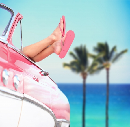 woman freedom: cool convertible vintage car and woman feet out of window against tropical see background with palm trees Stock Photo