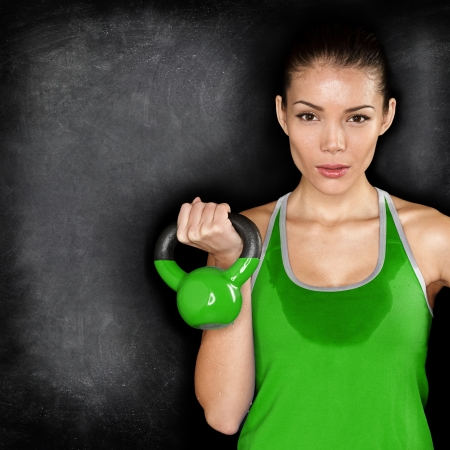 Fitness woman exercising crossfit holding kettlebell strength training biceps. Beautiful sweaty fitness instructor on blackoard background looking intense at camera. Asian Caucasian female model. Stock Photo