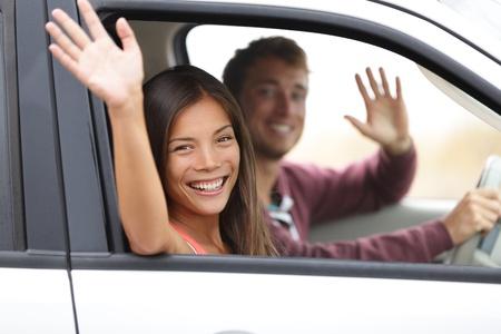 gente saludando: Drivers conducir en coche agitando feliz a la c�mara. Pareja joven en viaje por carretera en el nuevo coche. Interracial pareja feliz.