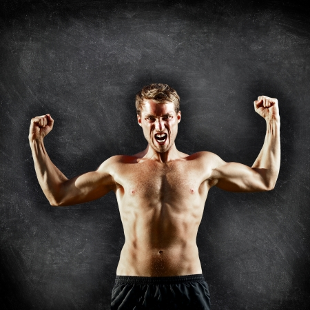 Crossfit fitness man flexing strong and aggressive showing muscles on blackboard background with copy space for text. Male cross fitness trainer on chalkboard background showing biceps muscles photo